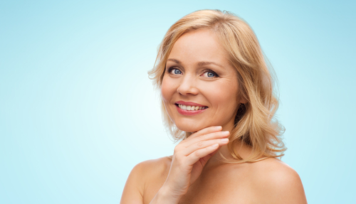 smiling middle aged woman with bare shoulders touching face-img-blog